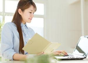 パソコンで作業する女性の画像